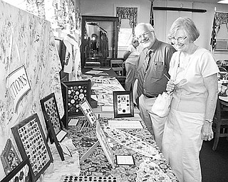 Special to The Vindicator COLLECTIBLES: A collection of buttons fascinates Dean and Betty Brown of Poland as they get a sneak preview of exhibits to be displayed during Heritage Day on Sunday at the Ward-Thomas Museum in Niles.
