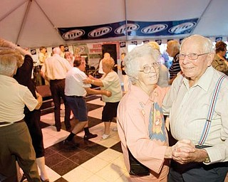 """LOVE OF DANCE: Grace, 88, and Harry Ripley, 94, of Campbell dance to the country song """"I Just Want to Dance With You"""" by George Strait at the Greater Youngstown Italian Festival. """"Wherever we can dance, we go,"""" Harry said. The couple visits the festival every year."""