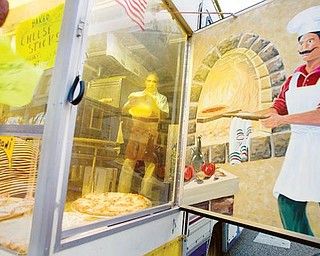 A REFLECTION OF THE PAST: Amico Colaizzi of Poland tosses pizza dough opposite a mural while inside Paisano's Pizza Connection at the Greater Youngstown Italian Festival downtown. The festival, on six city blocks, features entertainment, games and food. It continues today.