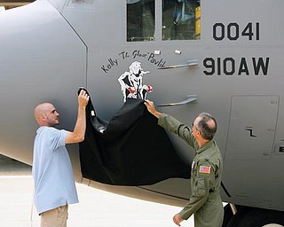 "NOSE JOB: World middleweight boxing champion Kelly ""The Ghost"" Pavlik and Col. Karl McGregor unveil Pavlik's logo on the nose of a C-130 Hercules cargo transport plane at the Youngstown Air Reserve Station. The artwork was done by Michele Kennedy of Warren, who has been in the Air Force Reserve for about four years."