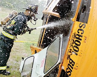 8.4.2009Firefighter/Medic, Chuck Wise, hoses down a school bus during an extraction exercise at the Liberty Fire Station along Logan Way on Tuesday afternoon.Geoffrey Hauschild