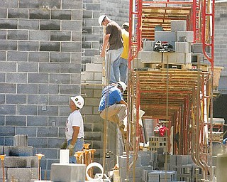 WALLS RISING: Workers from Lencik Masonry in Boardman lay cement block as the walls of the new Wilson Middle School in Youngstown begin to take shape.  The new school is being built on the same site as the former Wilson High School which was razed as part of a $190 million rebuilding program.