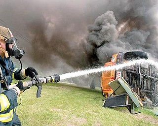 IN THE AFTERMATH: Liberty firefighter Jay Thompson waters down the undercarriage and tires of a bus set ablaze during a training exercise for firefighters and Liberty school district bus drivers. The program focused on how the two groups must work as a team in an emergency involving a school bus with students aboard.