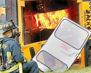 TRAINING: Liberty firefighter Chuck Wise watches the flames in an old school bus set afire as part of a training exercise. Firefighters learned where and how to cut into the reinforced buses. Newer buses have roof hatches and emergency window exits, which help in evacuations.