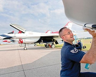 READY FOR SHOW: Staff Sgt. Chris McClure, number 4 assistant crew chief, wipes down an F-16 jet after the Air Force Thunderbirds arrived at the Vienna Air Base on Thursday in preparation for this weekend's air show.  McClure is one of 130 people involved in the Thunderbirds show. He joined the Air Force eight years ago and has been with the Thunderbirds for the last three.