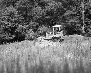 RESTORATION: A bulldozer moves dirt on the 48-acre site owned by the Mill Creek MetroParks system. The site, which used to be a sod farm, is being restored to its original wetland environment.