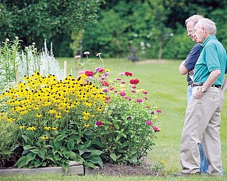 "Jack Fergus, left, and his father, John Fergus, both of Canfield, look at the gardens during the ""Connecting with Yourself, Nature and the Creator"" event in Canfield on Sarturday."
