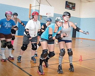 Mandy Tucker (second from right) squeezes past Natalie Clark (right), who tries to block her progress during a roller derby practice by the Little Steel Derby Girls at the Boys and Girls Club of Youngstown on Sunday evening.