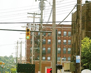 UGLY LINEUP: Youngstown State University wants Ohio Edison to remove these wooden utility poles from West Rayen Avenue and bury the wires where the university is building its $34.3 million business school, but the electric utility is balking at undertaking the task at the utility's expense.