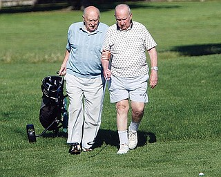 HELPFUL HAND:  Joe Shiller, left, leads Irv Fine, who is blind, down a fairway at the Par 3 Golf Course at the Wick Recreation Area of Mill Creek Park. Fine, 87, and a group of other veterans who are visually impaired play a round of golf at the course every Friday.