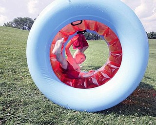 ON A ROLL: Isaiah Walter, 3, rolls down a hill in an inflatable tube at Mill Creek Park in Youngstown Monday. His father, Daniel Walter, of Youngstown, runs alongside the tube. With temperatures in the 90s Monday, Mill Creek Park seemed to be a popular place to beat the heat.