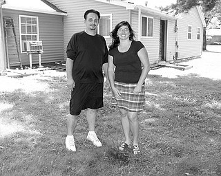 FEDERAL HELP: Christopher Wargo, left, and his wife, Alissa, stand at the rear of  their home on Pleasant Valley Road in Vienna Township. The small area  of dirt in front of them is the only indication on their property  that they even have a septic system. It empties into a ravine at the  back of their property. The couple has been approved to receive  federal stimulus money to replace the system, which didn't meet  regulations when the Wargos bought the house in 2005.