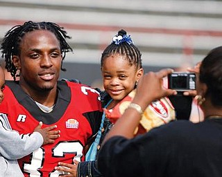 Lenny Wicks poses for his mom, Yvonne, holding his two children, 2-and-a-half old Lenny Jr. and 4-year-old Nevaeh at YSU's football photo day.