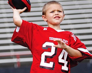 Jake Wright, wearing the famed #24 of YSU, tosses a few passes for his dad, Offensive Coach Brian Wright at football photo day at YSU.