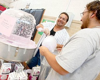 "SUGARY TREAT: Juan Luciano, of Campbell, and Francisco Morales, of Youngtown, volunteered at the Salvation Army on Glenwood Avenue during the ""Kids Fun Fair"" Wednesday afternoon. The pair bagged cotton candy, and Morales said his family has been involved with the organization for many years."