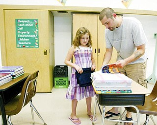 Taylor Simpson, 9, a soon-to-be- 4th grader at Immaculate Heart School in Austintown, gets help with her school supplies from her dad, Anthony Simpson, during a Monday open house at the school.