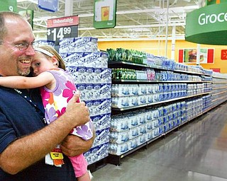 READY FOR SHOPPERS: Jason Steele of Austintown, a Wal-Mart associate who works in stock, hugs his 21-month-old daughter, NancyRose, as they walk through aisles of the new store that opens today. An open house took place Tuesday for business people, community leaders and family and friends of store employees. Steele was laid off from Delphi Packard Electric.