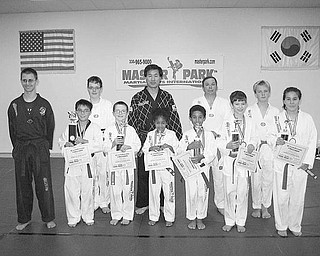 Special to The Vindicator REGIONAL CHAMPS: Students of Master Park Martial Arts International display trophies they won by competing in various forms of marital arts at the regional U.S. Martial Arts Championship event. Pictured above after the competition are, from left,in front, Craig Mihalik, William Anderson, Wyatt Miller, Smeera Murad, Zeemeer Murad, Isaiah McInnis and Samantha Anderson; and, in back, Tommy Sodeman, Master Park, Dr. Richard Bacha and Richard Abel. Also winning trophies but not pictured with the champions are Evan Croutch, Jimmy Vaugh, Aaron Patton and Alan Petragel. Below, Evan Croutch demonstrates how he won the breaking competition with a flying jumping sidekick over obstacles.
