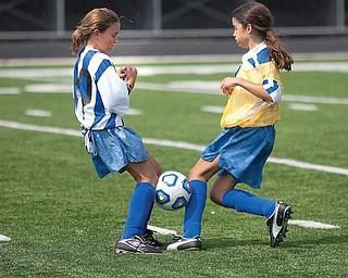 The Vindicator/Geoffrey HauschildA soccer ball gets stuck as Justine Kramer challenges Jillian Penman for the ball during a game at Poland High School.8.15.2009