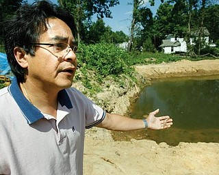SHRIMPING: Ron Eiselstein of Youngstown gestures toward the pond on the city's far East Side where he is growing Malaysian prawn, which are freshwater shrimp. In his hand he is holding a shell or skin the prawn leaves behind when it molts.
