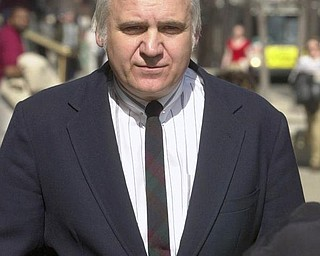 file - In this April 11, 2002  file photo, U.S. Rep. James Traficant Jr. arrives at the federal courthouse in Cleveland to hear the verdict in his bribery and corruption trial.   Traficant, the wild-haired ex-congressman nearing release from prison after serving a sentence for corruption, will return to a hometown that has ample evidence of the federal aid he landed, including a highway, second federal courthouse and an arena. (AP Photo/Mark Duncan, File)