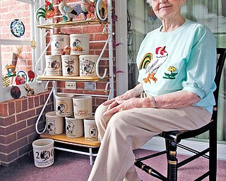 """FAIR COLLECTOR:  Eileen Groves, a Canfield native, sits in her home in front of a collection of 13 commemorative crocks featuring the Canfield Fair rooster mascot and slogan, """"Something to crow about."""" Groves now resides at Copeland Oaks Retirement Community in Sebring."""