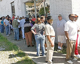 TILE ENTHUSIASTS: Dozens of people stand outside a vacant tile store on Mahoning Avenue. The old Wall Tile Co. hasn't served customers in more than a year and the building's landlord treated more than 100 people to the tile and supply contents of the building free of charge Wednesday.