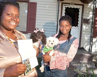 TREASURED MEMENTO: Tina Fleisher holds a letter from Michelle Obama and a photo of Bo, the Obamas' Portuguese water dog, that she received from the White House. Her daughter, Cleopatra Butler, cradles the family's pet poodles, Diamond Louise and Jamie Foxx, who produced two puppies that the Fleishers had offered to the Obama family.