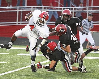 STRUTHERS - GIRARD - (4) Kevin McDonald of Struthers breaks away from (2) Dan Graziano (35) Josh Alexander and (22) Daitzel Moore during their game Friday night. - Special to The Vindicator/ Nick Mays