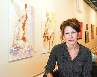SALEM GALLERY: Kristina Danklef Moore sits near two of her paintings at DH Gallery in Salem. The recently reopened gallery is at 515 E. State St.
