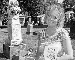 """REAL-LIFE MYSTERY: Karen Biery of Salem holds a copy of her first book, """"believe."""" Behind her is the grave of Goldie Bell Taylor, who died in 1886. Biery was inspired to write her book because an unidentified person has been leaving flowers at Taylor's grave in Hope Cemetery."""