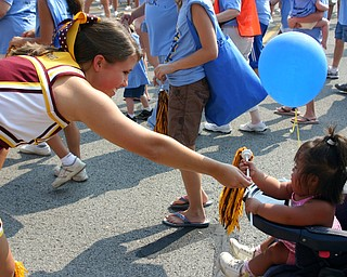 South Range Senior cheerleader Jesse Heck passes out pom-poms at the