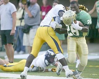 The Vindicator/Robert K. Yosay ---Ursulines #28 Allen Jones looses his helmet as he crossed the goal line -as Viking #8 Malik Johnson fails to bring him down during first quarter action at  Wheeling Island Stadium 952009
