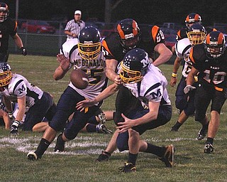 MCDONALD - MINERAL RIDGE - (15) Miles Dunlap (55) Trent Clay fight for a lose ball as (60) Brian Sherba tries to make the play during their game Friday night. - Special to The Vindicator/Nick Mays