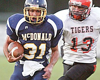 McDonald'sZach Tura eludes Wellsville's Bubba Dowling  to score durings 1 rst qtr at McDonald. WDLEWIS