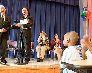 """WITH HONOR: McGuffey Elementary kindergartners Bernard Thomas, right, and Timothy Davis applaud as Richard Scarsella, president of the William Holmes McGuffey Historical Society, honors Gilbert """"Gibby"""" James of Canfield, far left, with the fourth annual Pioneer Award. The award is given to local individuals for notable contributions to literacy and historical preservation of the Mahoning Valley."""
