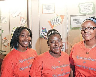 PEACEMAKERS: Youngstown students, from left, Mallory Kimble, Janae Ward and A'Ja Glover, stand in front of a message board at Chaney Middle School featuring quotes on nonviolence. The three organized a project to reduce violence in their schools.