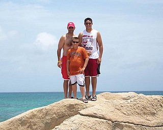 Ron, Keary and AJ Iarussi of Struthers stand on some rocks overlooking the ocean in Aruba.