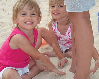 Allison and Lindsay Jones, 4, buried their cousin Isabella's feet in the sand while in Gulf Shores, Ala., in July.