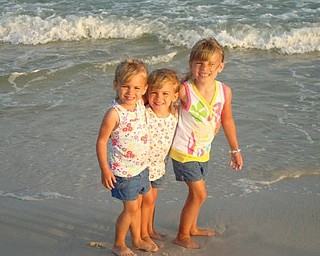 Lindsay and Allison Jones, 4, and Samantha Jones, 5, are enjoying their first time at the beach in July in Alabama.
