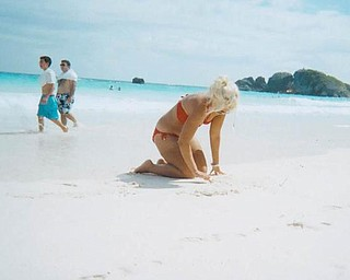 Corrie Lynn Romesburg, daughter of Darlene Romesburg of Struthers and Steve Romesburg of Warren and a YSU freshman, is shown writing in the sand at Horseshoe Bay in the Bermuda. She traveled to Bermuda to attend the wedding of her cousin.