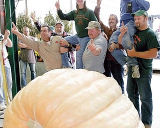 WE ARE THE CHAMPIONS: Christy Harp and her husband, Nick, are lifted up after setting a record for heaviest pumpkin at The Ohio Valley Giant Pumpkin Growers weigh-off. The Massillon couple's pumpkin weighed 1,725 pounds at the event Saturday at Parks Garden Center in Greenford.