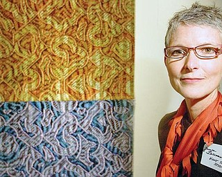 "ELEMENTS: Janice Lessman-Moss, curator of the ""Touch and Scale"" art display, stands near her weaving combination of silk, nylon, paint and ink that she calls ""Elements."" The piece is part of an exhibit of artwork from Kent State University students and faculty."