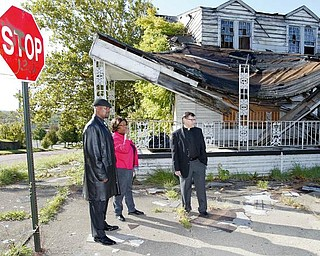 TAKE IT DOWN: ACTION, a faith-based, grass-roots community organization, wants Youngstown to demolish the long-vacant Linton Funeral Home on the North Side. Among those calling for the building to come down are, from left, Byron Armour, a North Side resident; Rose Carter, an ACTION organizer, and Pastor Joseph Rudjak of Sts. Peter and Paul Church.