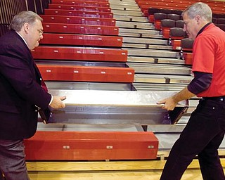 A NEW NOTION: Canfield Local Schools Superintendent Dante Zambrini, left, assists high school athletic director Greg Cooper with a removable first step to the school gymnasium's new bleachers. The school district completed a renovation project, which cost about $300,000, and replaced the gym floor as well as the bleachers.