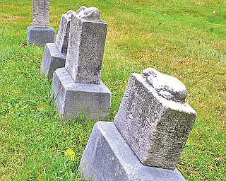 Four tiny stone markers of those taken away too soon