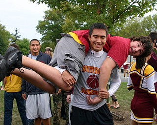 """Peter Dinh hoists a friend at the Blitz tailgate party."""