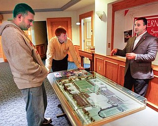SUPER MODEL: Austintown Superintendent Vince Colaluca, right, explains to Rich Klena, left, the model of the proposed campus-style layout for the school district if a 2.9-mill bond issue passes next month. In the center is the Rev. Rick Stauffer, pastor of Tabernacle Evangelical Presbyterian Church, where a town-hall meeting took place. If passed, the bond issue would fund the 53 percent local share of a $50 million expansion project.