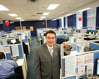 NEW HOME: Chris Butcher, senior operations manager at VXI Global Solutions, stands among new operators at the company's downtown call center. Butcher, a Mahoning Valley native, was working in Los Angeles when he suggested VXI consider Youngstown for a call center.