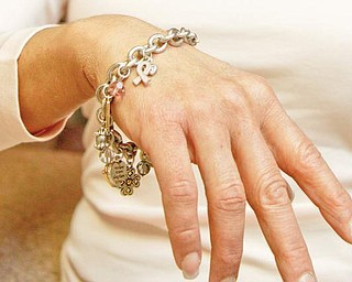 SYMBOL OF LIFE: Castranova models a charm bracelet with a breast-cancer symbol. October is Breast Cancer Awareness Month, and Castranova said her self-exam might have saved her life.